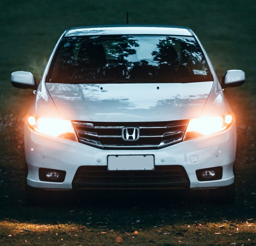 Photo of front view of white honda car with headlights on at dusk